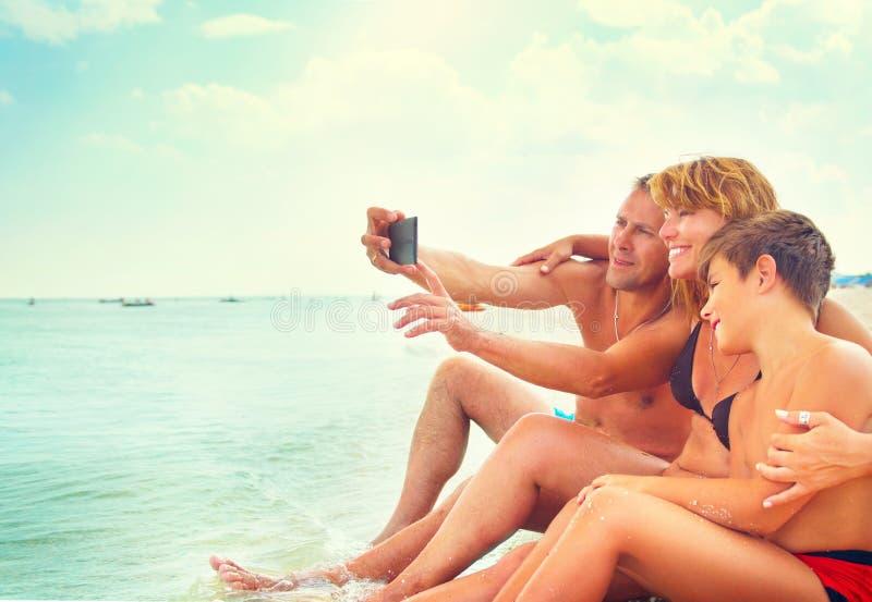 Família nova feliz que senta-se na praia e que toma o selfie fotografia de stock