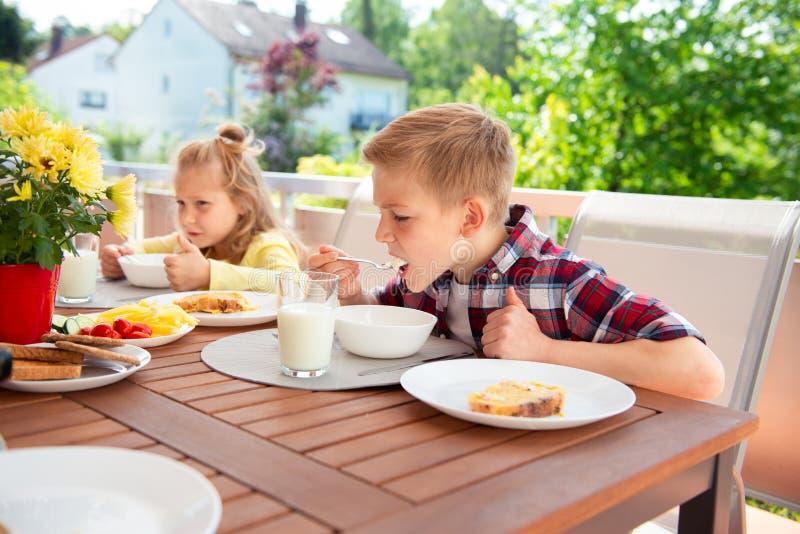Família nova feliz que tem o divertimento durante o café da manhã no terrasse em ho imagem de stock
