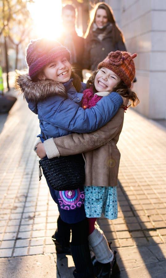 Família nova feliz que tem o divertimento na rua imagem de stock