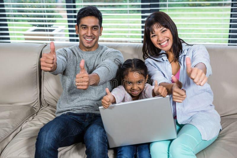 Família nova feliz que usa o portátil com polegares acima fotografia de stock royalty free