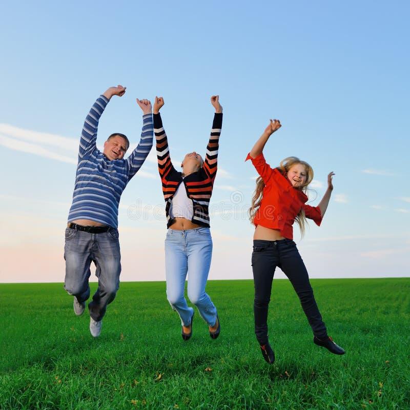 A família nova feliz salta para a alegria imagem de stock royalty free