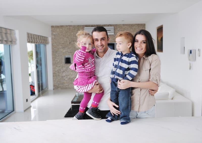 A família nova feliz tem o divertimento em casa imagens de stock