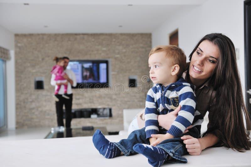 A família nova feliz tem o divertimento em casa imagens de stock royalty free