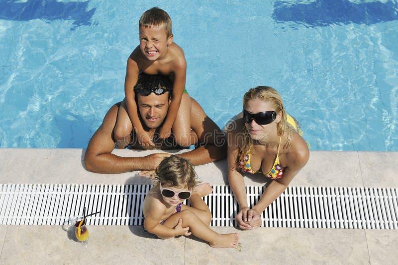 A família nova feliz tem o divertimento na piscina