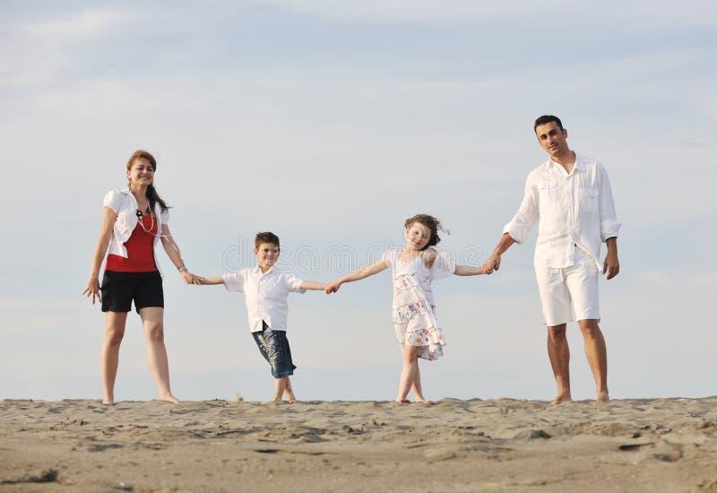 A família nova feliz tem o divertimento na praia imagens de stock royalty free