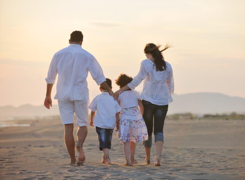 A família nova feliz tem o divertimento na praia fotografia de stock royalty free