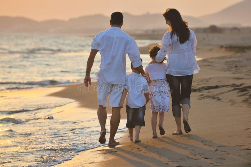 A família nova feliz tem o divertimento na praia foto de stock royalty free