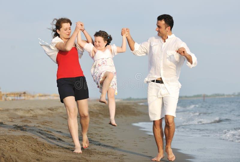 A família nova feliz tem o divertimento na praia no por do sol foto de stock royalty free