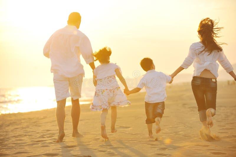 A família nova feliz tem o divertimento na praia no por do sol imagens de stock royalty free