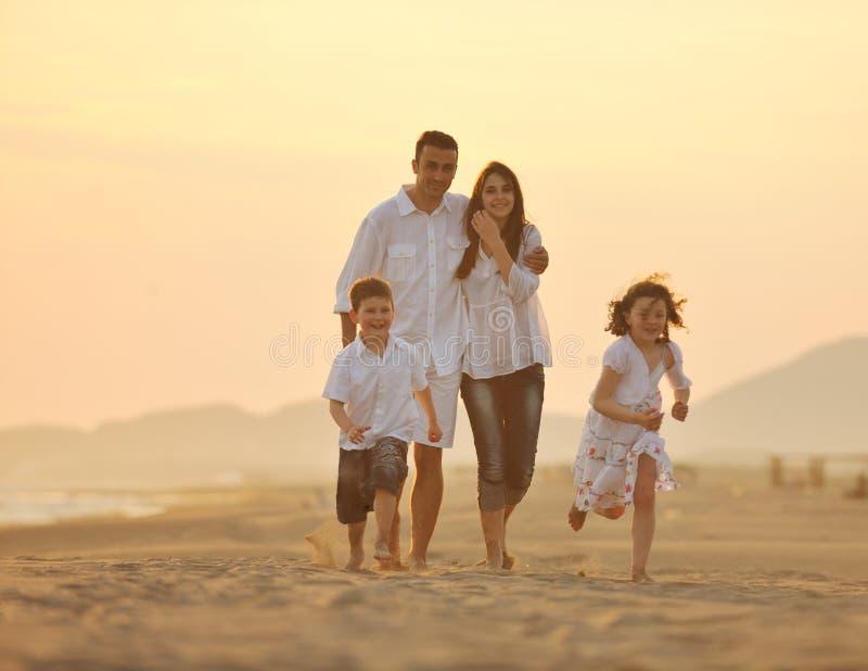 A família nova feliz tem o divertimento na praia no por do sol fotografia de stock royalty free