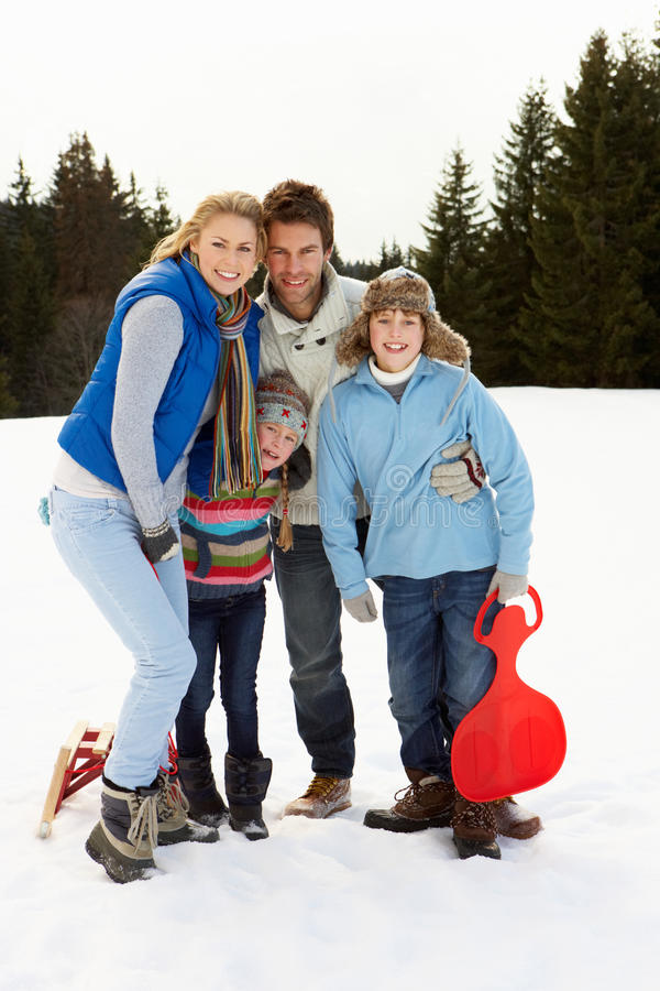 Família nova na cena alpina da neve com trenós fotografia de stock