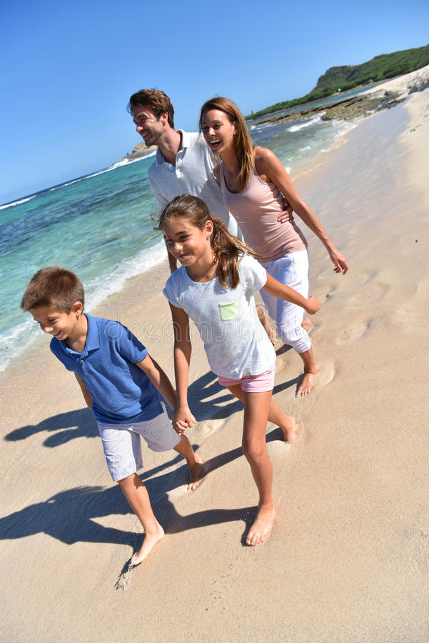 Família nova que anda no dia de verão bonito do ona da praia fotografia de stock