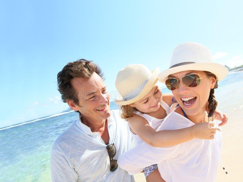 Família nova que aprecia suas férias de verão na praia fotos de stock