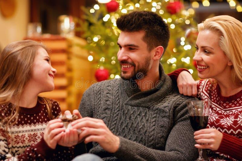 Família nova que comemora e que troca o Natal dos presentes em casa imagem de stock royalty free