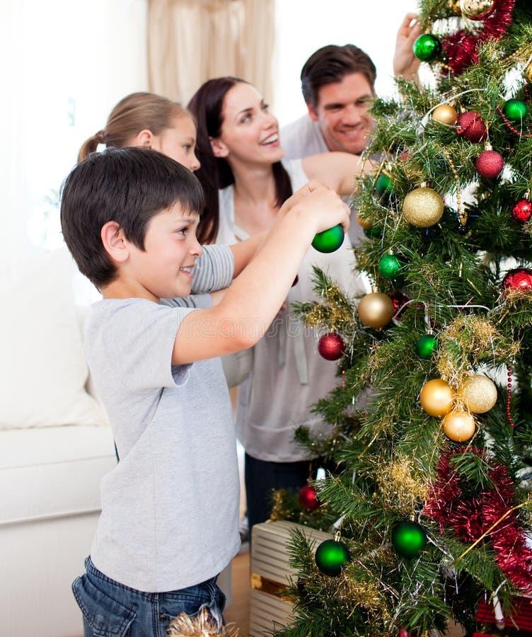 Família nova que decora uma árvore de Natal imagem de stock royalty free