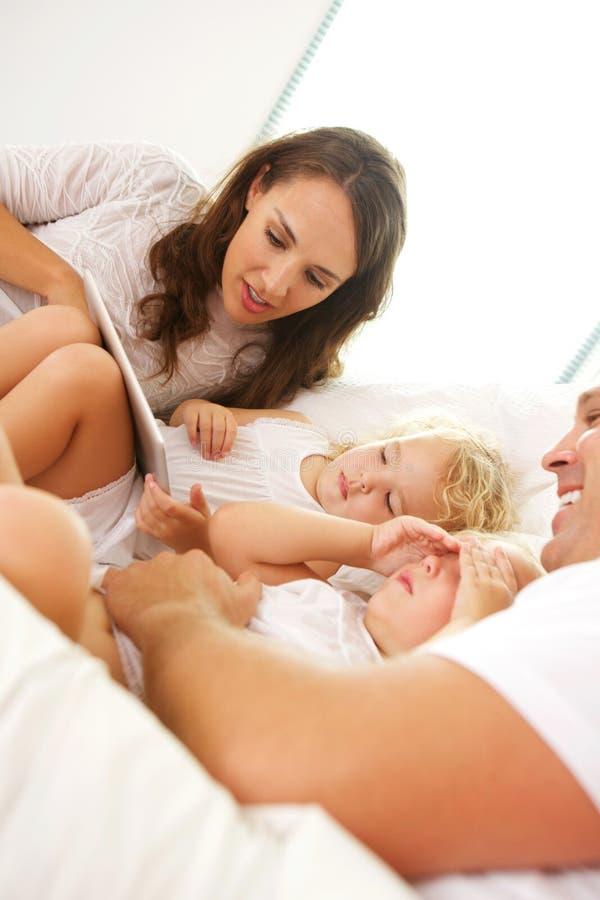 Família nova que encontra-se na cama com tabuleta digital fotografia de stock