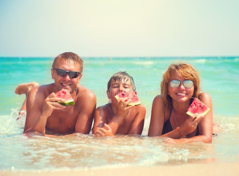 Família nova que encontra-se na praia e que come a melancia imagens de stock