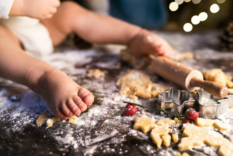 Família nova que faz cookies do pão-de-espécie em casa imagens de stock