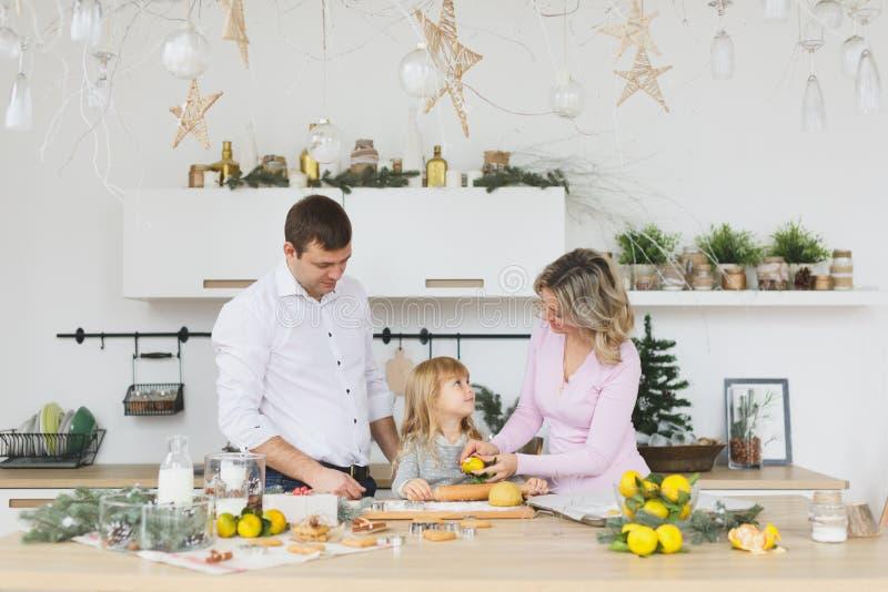 Família nova que faz cookies em casa conceito do alimento, da família, do Natal, do hapiness e dos povos - família de sorriso que fotografia de stock
