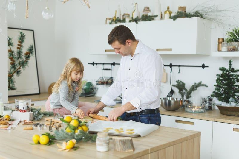 Família nova que faz cookies em casa conceito do alimento, da família, do Natal, do hapiness e dos povos - família de sorriso que foto de stock