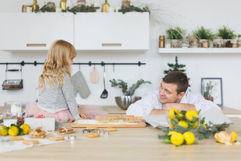 Família nova que faz cookies em casa conceito do alimento, da família, do Natal, do hapiness e dos povos - família de sorriso que fotos de stock