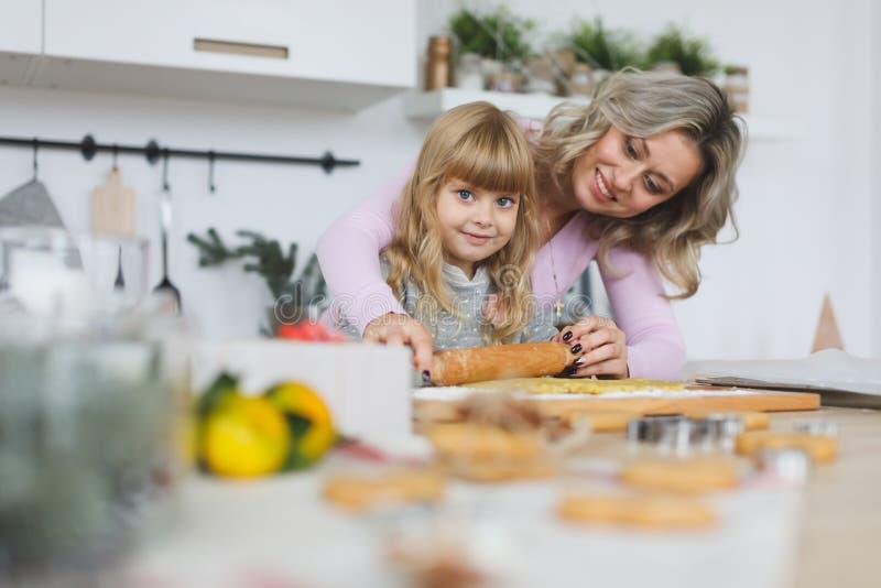 Família nova que faz cookies em casa conceito do alimento, da família, do Natal, do hapiness e dos povos - família de sorriso que imagens de stock royalty free