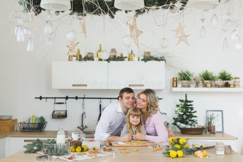 Família nova que faz cookies em casa conceito do alimento, da família, do Natal, do hapiness e dos povos - família de sorriso que imagens de stock