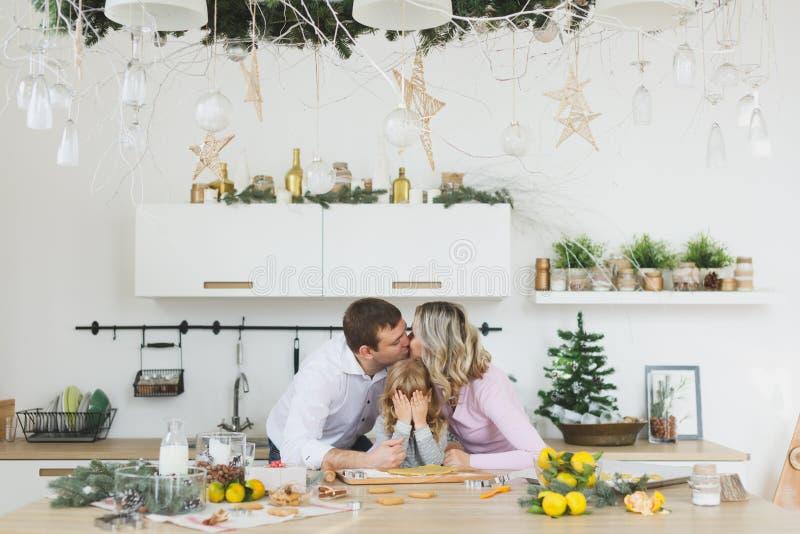 Família nova que faz cookies em casa conceito do alimento, da família, do Natal, do hapiness e dos povos - família de sorriso que imagem de stock