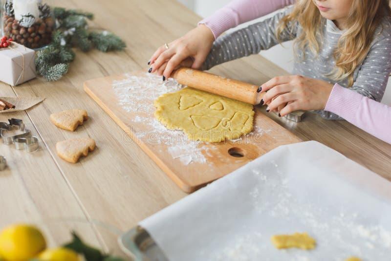 Família nova que faz cookies em casa Fazendo uma cookie do pão-de-espécie com as crianças no tempo do Natal fotografia de stock