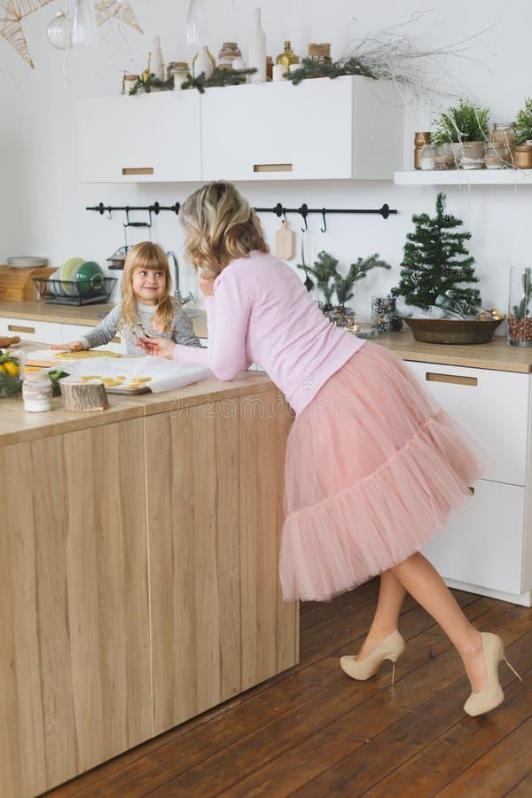 Família nova que faz cookies em casa Fazendo uma cookie do pão-de-espécie com as crianças no tempo do Natal imagens de stock royalty free