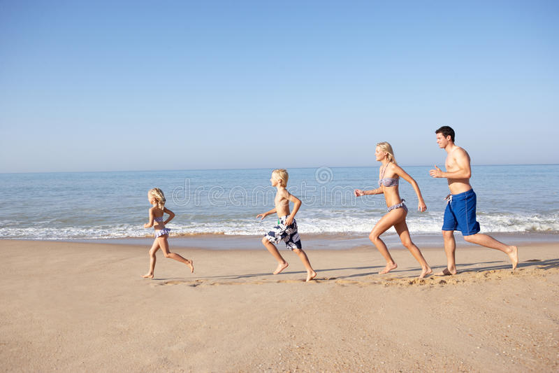 Família nova que funciona na praia imagens de stock