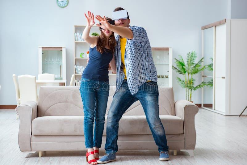 A família nova que joga jogos com vidros da realidade virtual foto de stock
