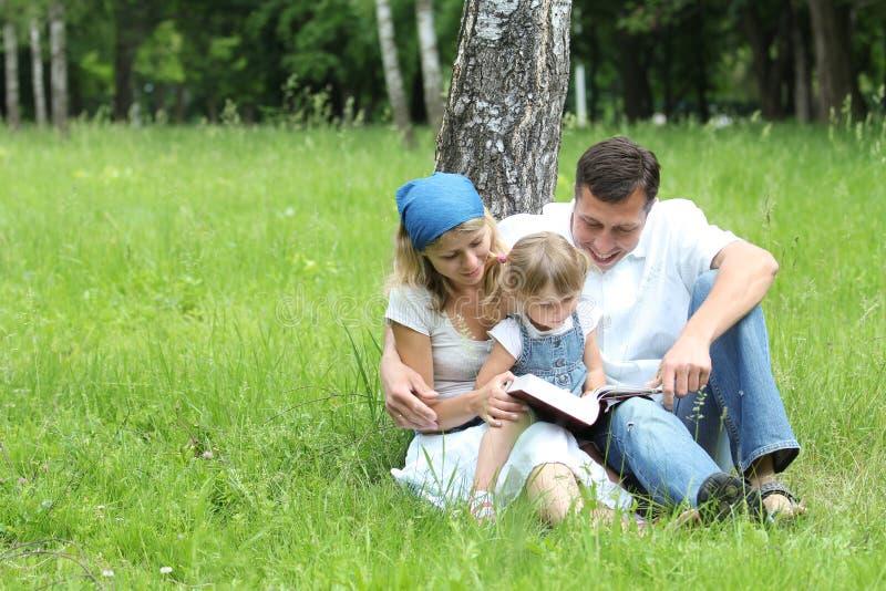 Família nova que lê a Bíblia fotografia de stock
