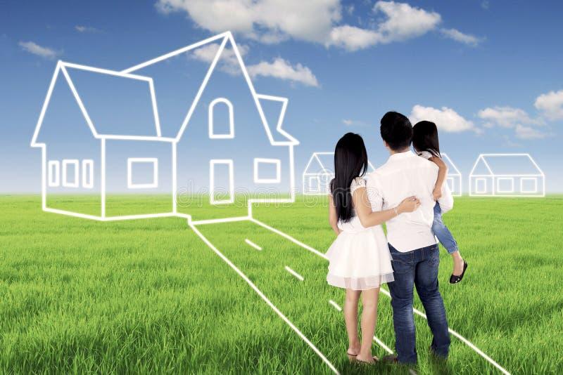 Família nova que olha sua casa ideal imagens de stock royalty free