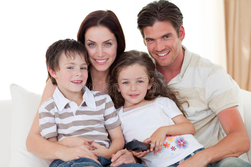Família nova que presta atenção à tevê no sofá fotos de stock royalty free