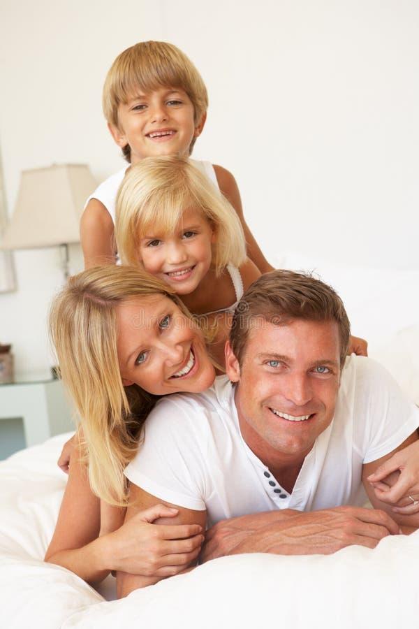 Família nova que relaxa na cama junto imagem de stock