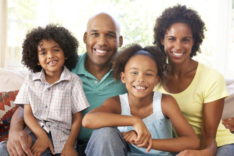 Família nova que relaxa no sofá em casa fotografia de stock royalty free