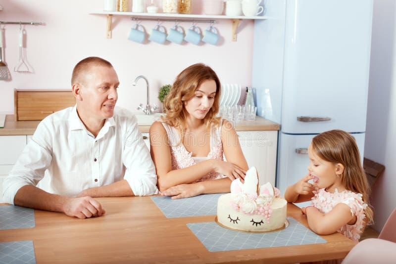 Família nova que senta-se na cozinha na tabela fotos de stock royalty free