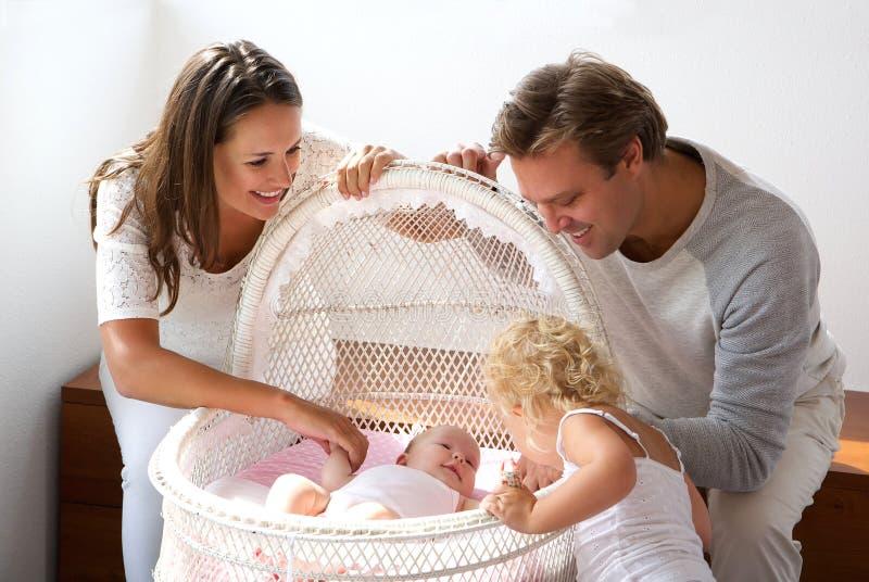 Família nova que sorri em recém-nascido no berço fotos de stock royalty free