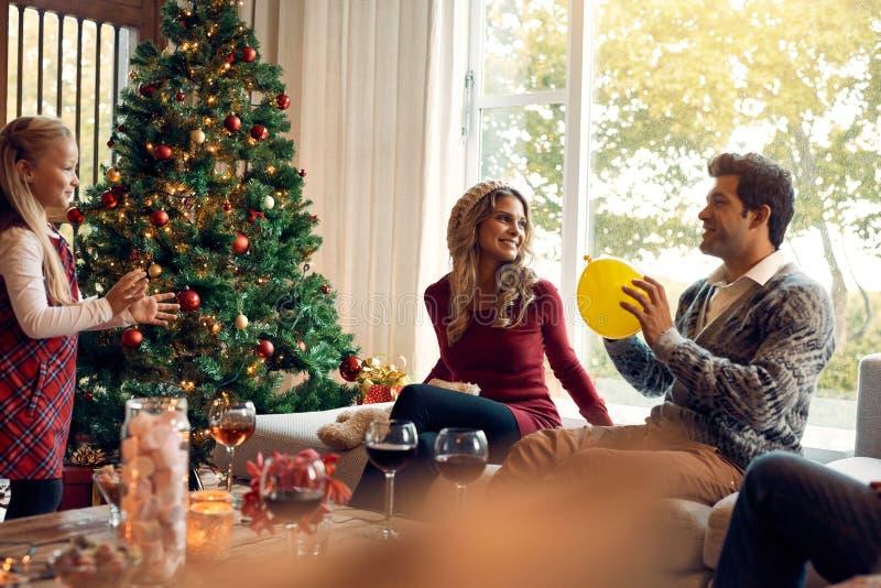 Família nova que tem o divertimento em casa durante o Natal fotografia de stock