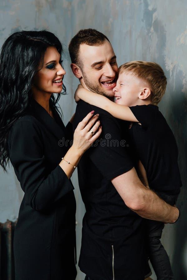 A família nova que tem o divertimento em casa em um fundo de um vintage textured a parede foto de stock royalty free
