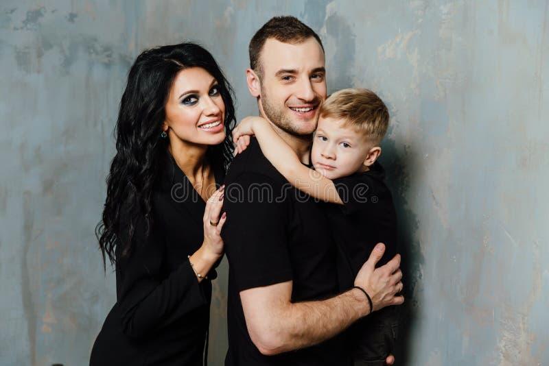 A família nova que tem o divertimento em casa em um fundo de um vintage textured a parede foto de stock