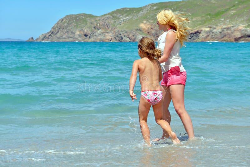 Família nova que tem o divertimento na praia fotos de stock