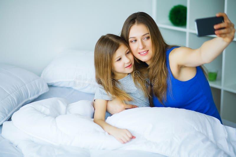 Família nova que toma o selfie com o smartphone na cama fotos de stock