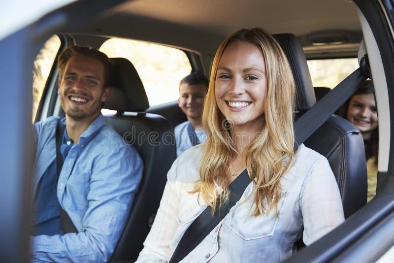 Família nova que vai no feriado em um olhar do carro à câmera fotografia de stock