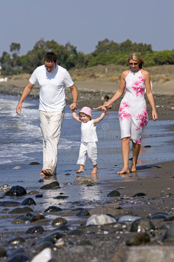 Família nova, saudável que anda ao longo de uma praia ensolarada fotografia de stock