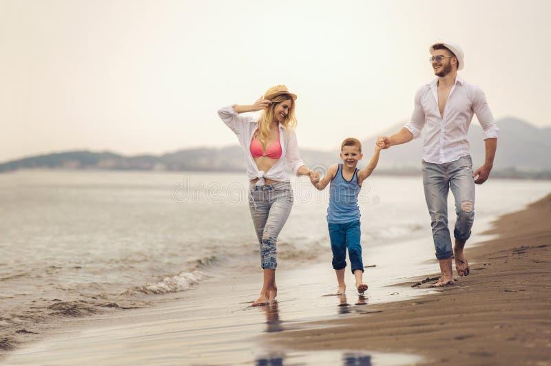 A família nova tem o divertimento na corrida e no salto da praia fotografia de stock royalty free