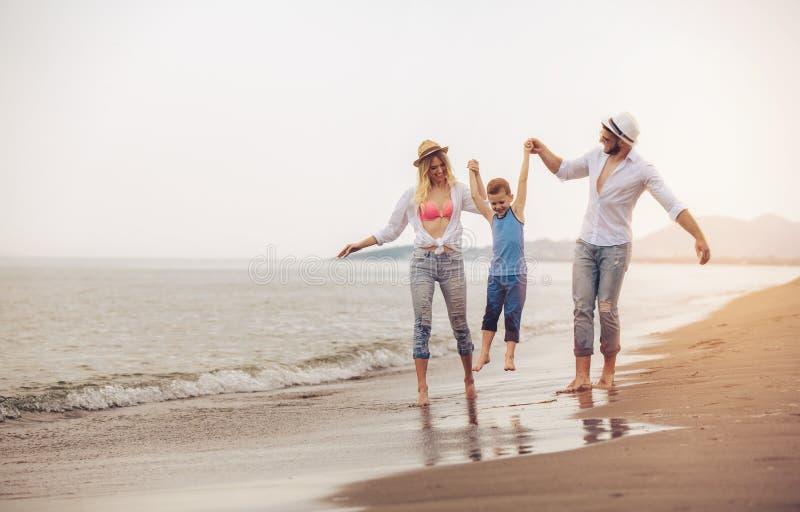 A família nova tem o divertimento na corrida e no salto da praia imagens de stock