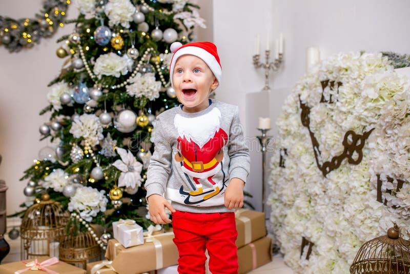 Família, pai, mãe e filho novos felizes, na noite do Natal na casa Um rapaz pequeno no suporte do chapéu de Santa perto da árvore imagem de stock royalty free