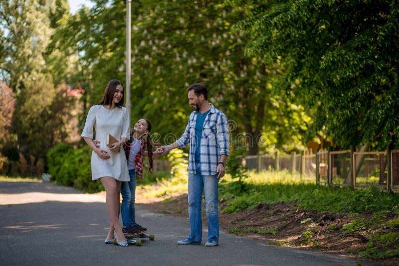 A família passa o tempo no parque da cidade Pai Is Helping Daughter a montar no skate no parque fotografia de stock royalty free